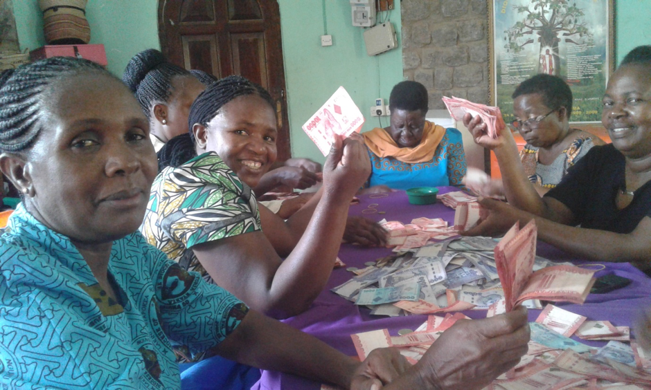 Women in Tanzania counting out money before they share it out to one of their group members.