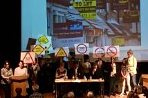 A group of children and adults standing on a stage with placards. Two people stand at a lectern while a picture of several houses with 'to let' signs is projected behind them.