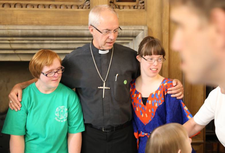 Justin Welby with two members of Hand in Hand worship group