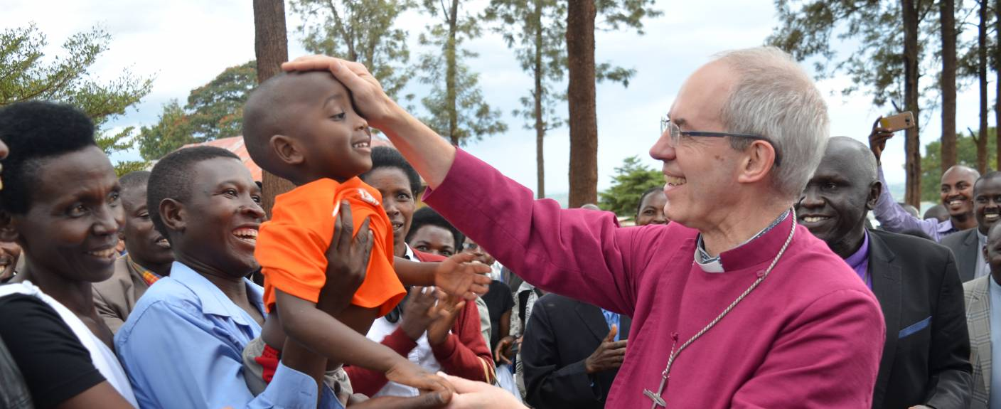 Justin Welby blesses a young child in Gahini, Rwanda