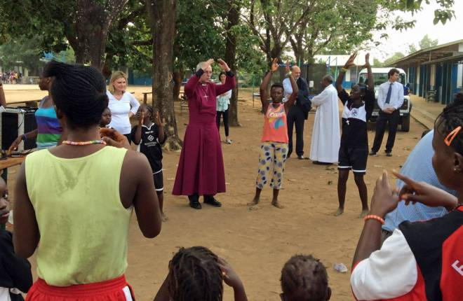 Archbishop Justin Welby singing with children at a church-run centre for children affected by Ebola.